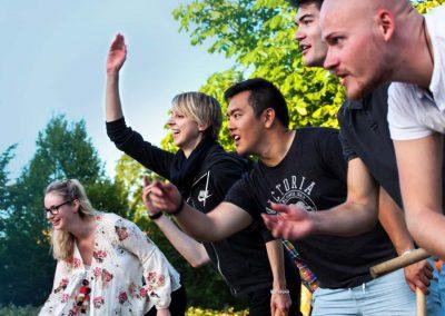 Personal och studenter spelar kubb ihop under en social kväll