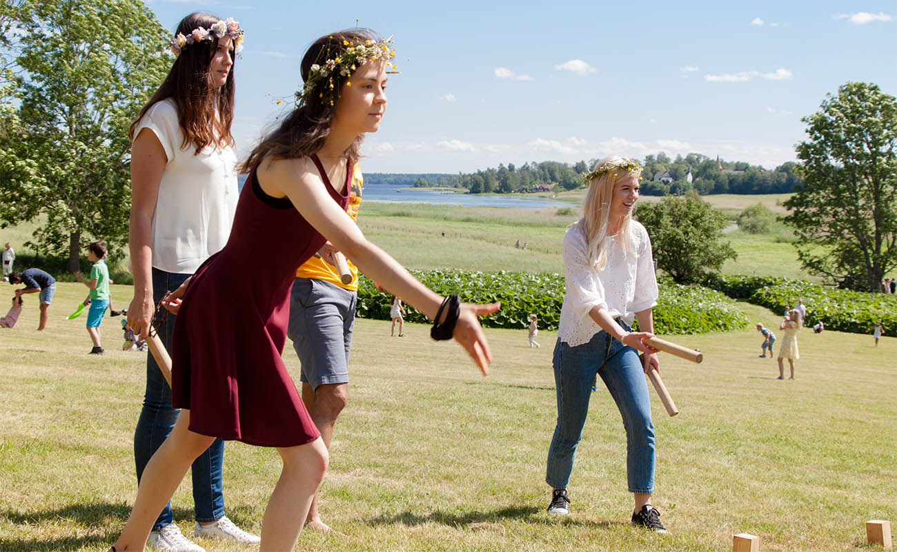 "Students playing the traditional Swedish game ""Kubb"" on Midsummer's Eve"